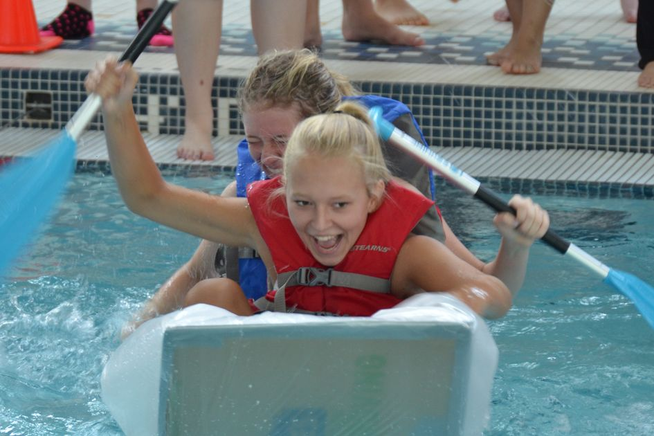 Two girls paddle a cardboard canoe in a pool.